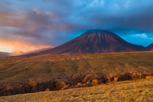Volcan Licancabar at sunset with breaking storm, Chile.
