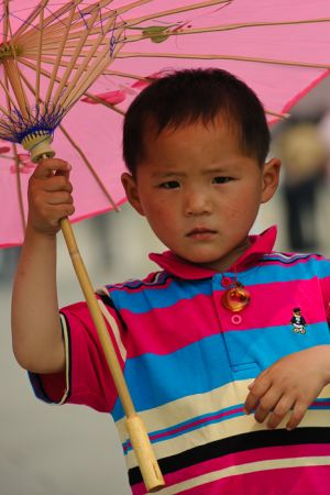Child with umbrella in Tiananmen Square, Beijing.
