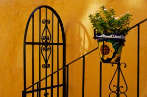 Railing and shadow on orange wall, Guanajuato, Mexico.